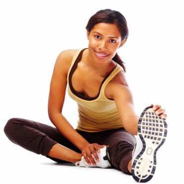 Fit young woman doing stretching exercise and smiling on white